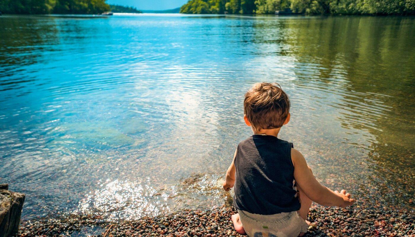 toddler sitting at lake